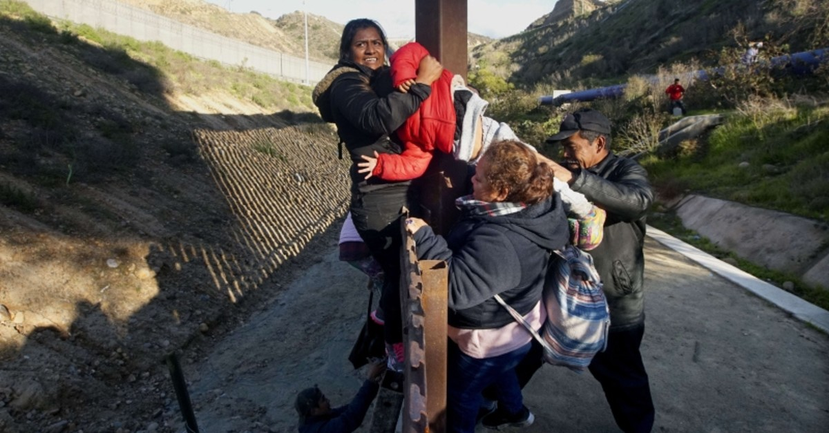 Honduran migrants climb over the U.S.-Mexico border fence along on Jan. 6, 2019 in Tijuana, Mexico (AFP Photo)