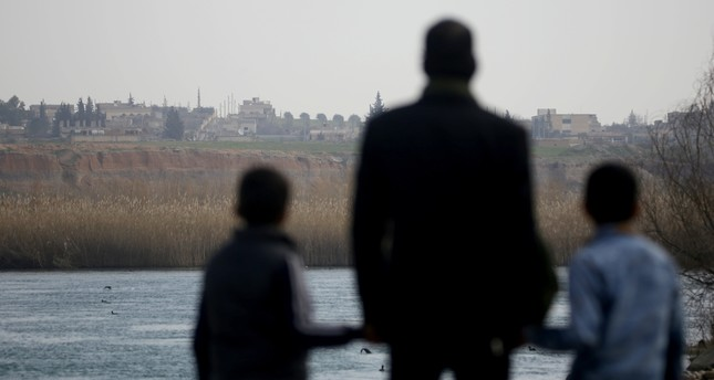 Mohamed Abu Ibrahim looks at his hometown Shuyukh on the eastern banks of the Euphrates River alongside his children, Feb.1, 2019.
