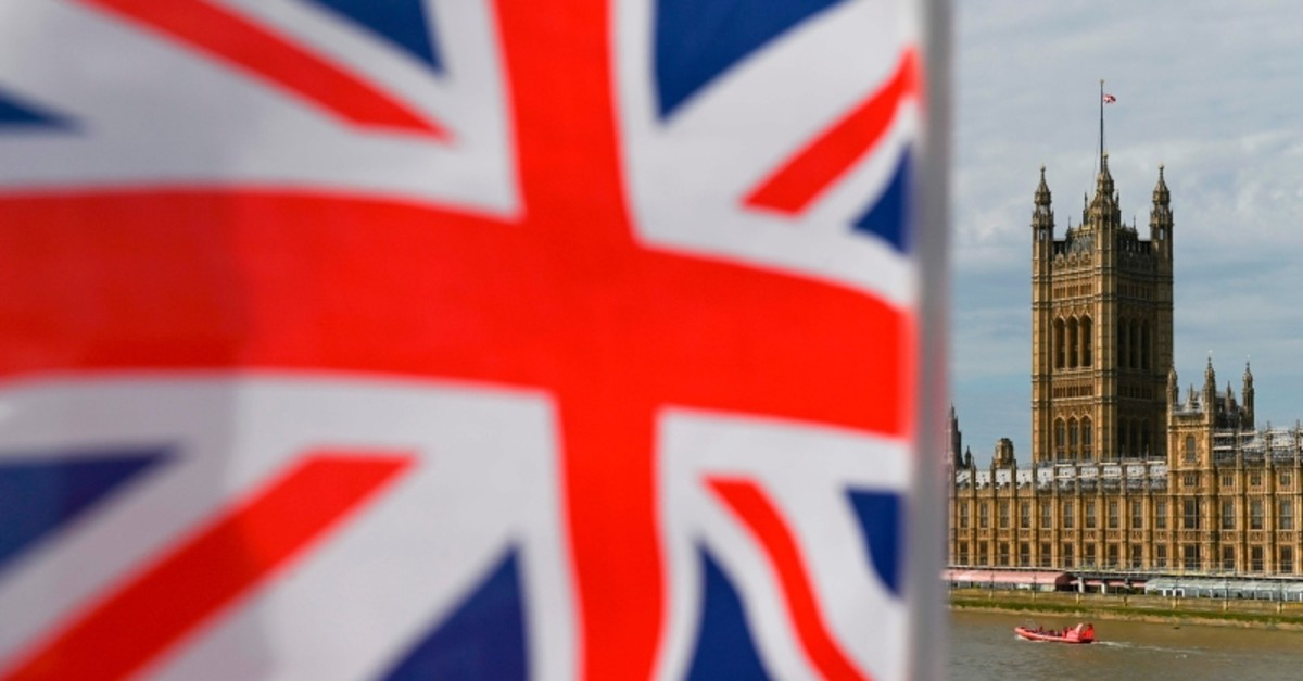 The Palace of Westminster housing the Houses of Parliament is seen from Westminster Bridge with a Union Flag in the foreground in central London on August 28, 2019 (AFP Photo)