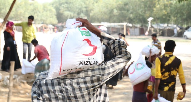 A man carries a bag with food aid distributed by the Turkish Red Crescent at a camp for Rohingya Muslims in Bangladesh in this undated photo.