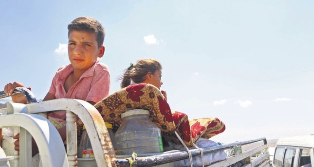 Syrians ride with their belongings in a pickup truck as they head to safer areas in Syria's Idlib province after fleeing regime attacks, Sept. 6.