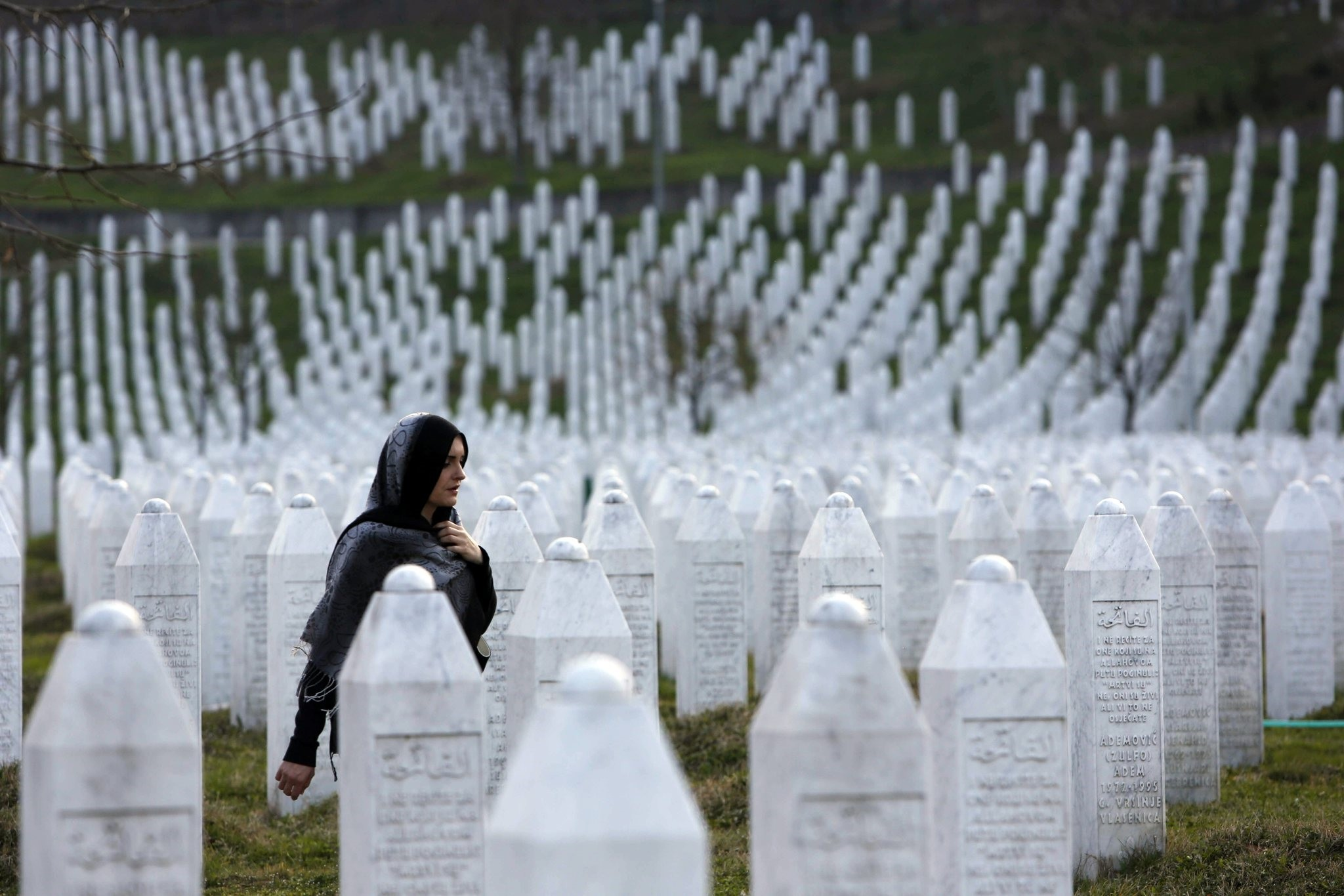 Bosnian woman walks among gravestones at Memorial Centre Potocari near Srebrenica, Bosnia and Herzegovina. (AP Photo)