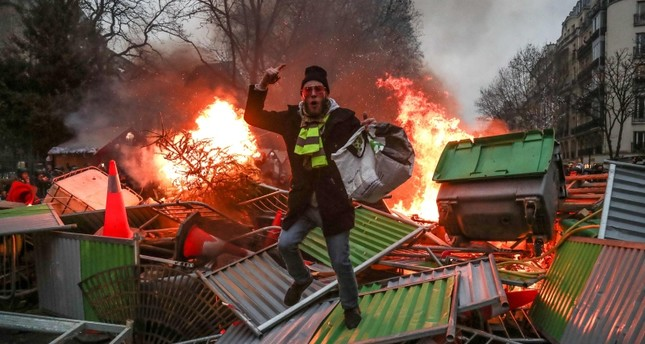 A yellow vest Gilets Jaunes anti-government protestor stands on a burning barricade in Paris on January 5, 2019 during clashes with security personnel. (AFP Photo)