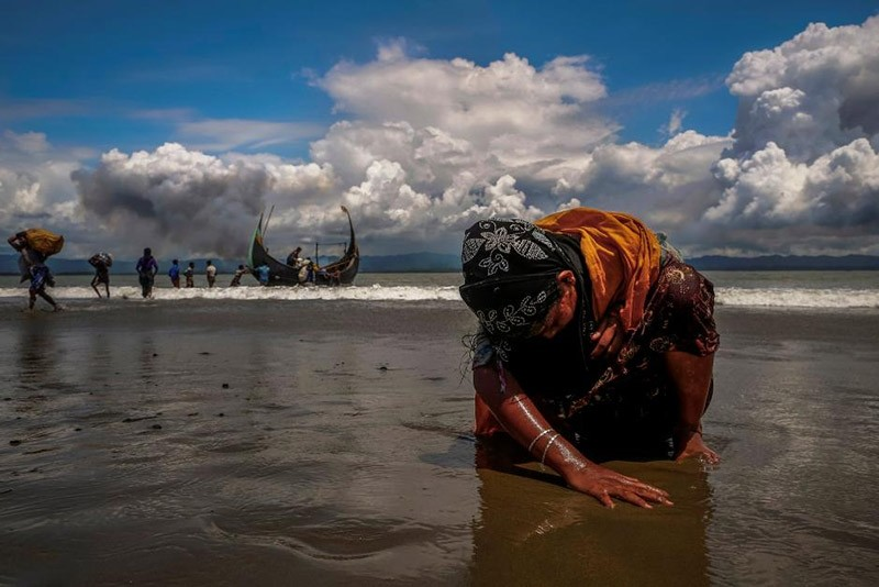 An exhausted Rohingya refugee woman touches the shore after crossing the Bangladesh-Myanmar border by boat through the Bay of Bengal, in Shah Porir Dwip, Bangladesh September 11, 2017. (Reuters Photo)