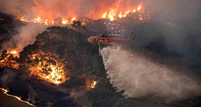 A handout photo taken and received on Dec. 31, 2019, from the State Government of Victoria shows a helicopter fighting a bushfire near Bairnsdale in Victoria's East Gippsland region. AFP Photo/ State Government of Victoria