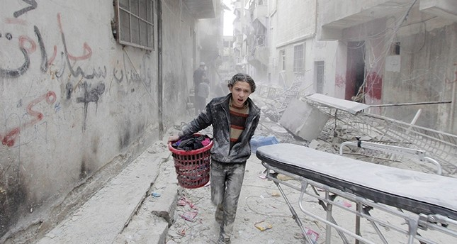 A boy carries his belongings at a site hit by a barrel bomb dropped by  Syria's Bashar Assad forces in Aleppo's al-Fardous district, Syria April 2, 2015. (Reuters Photo)