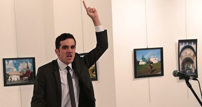 A man gestures after shooting Andrei Karlov, the Russian Ambassador to Turkey, on the floor, at a photo gallery in Ankara, Turkey, Monday, Dec. 19, 2016. (AP Photo)