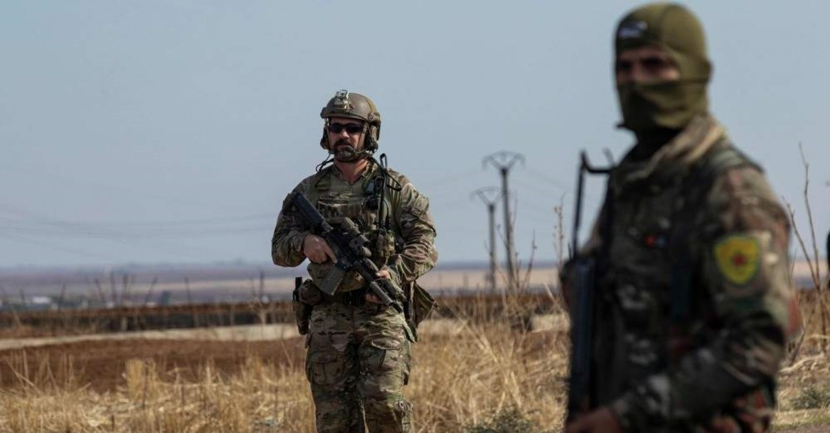 A U.S. soldier (L) and a masked member of the PKK-affiliated YPG during a patrol of the northern countryside of al-Malikiyah near the border with Turkey, on Nov.3, 2019. (AFP Photo)