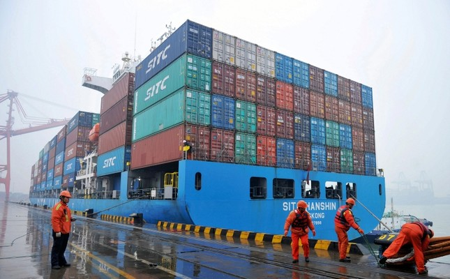 In this Friday, Jan. 11, 2019, photo, workers moor a container ship at a port in Qingdao in east China's Shandong province (Chinatopix via AP)