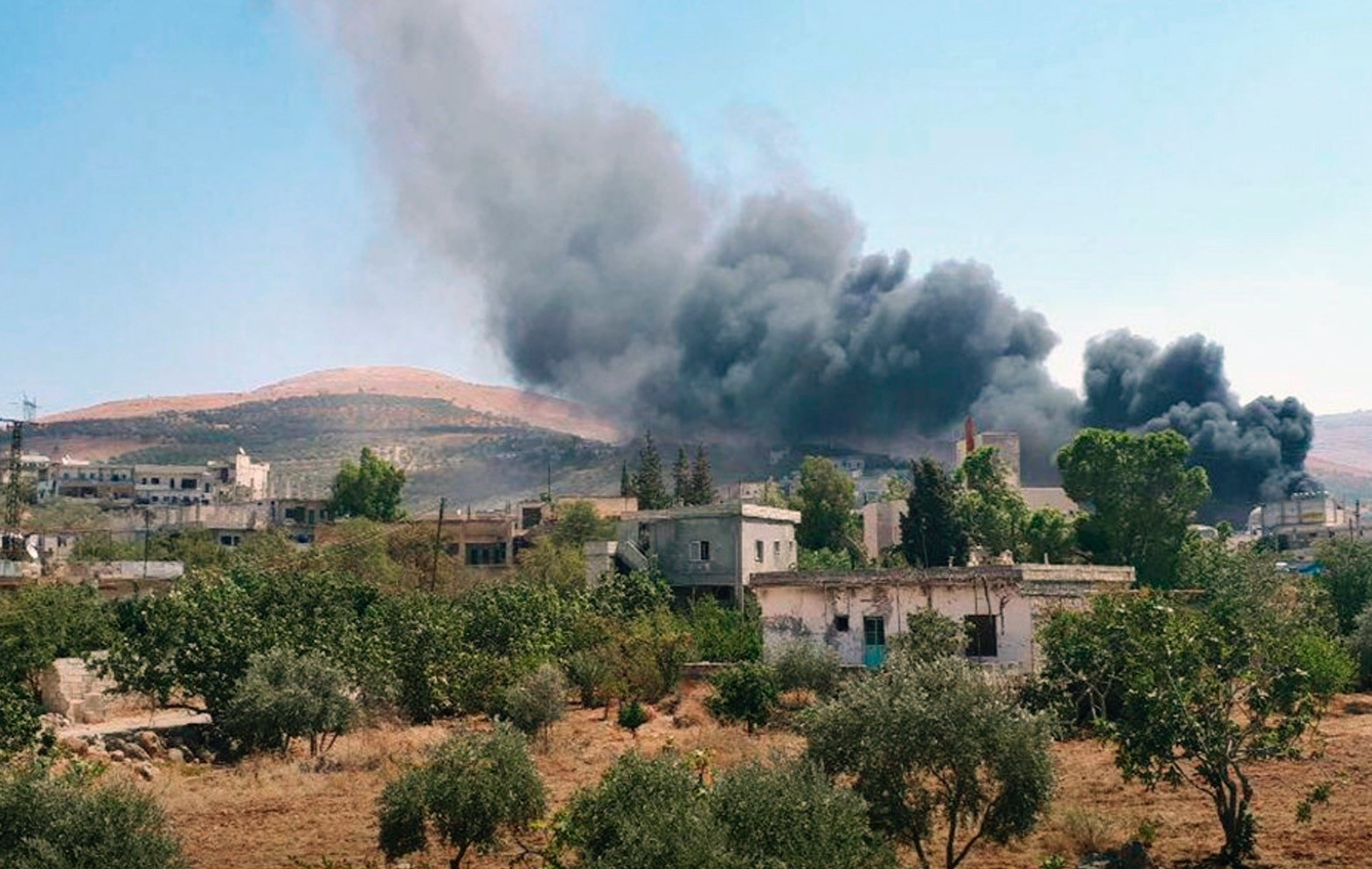 Smoke rises over buildings hit by airstrikes in Mahambal village in the northern province of Idlib, Syria.