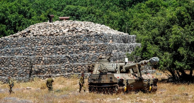 Israeli soldiers walk past a bunker with a mobile artillery piece seen deployed near the border with Syria in the Israeli-occupied Syrian Golan Heights on July 1, 2018. (AFP Photo)