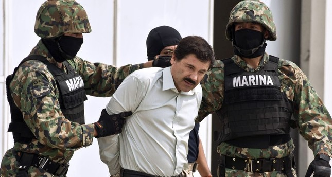 In this file photo taken on February 22, 2014 Mexican drug trafficker Joaquin Guzman Loera aka el Chapo Guzman (C), is escorted by marines as he is presented to the press in Mexico City. (AFP Photo)