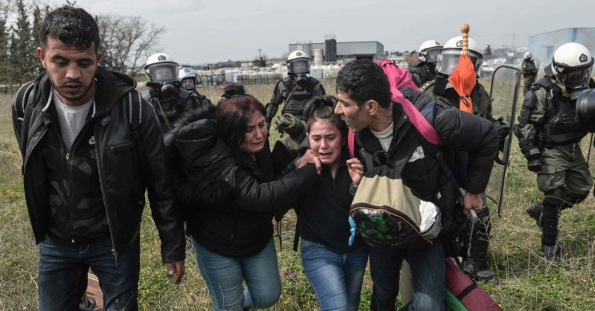 A family run as Greek riot police throw tear gas outside of a refugee camp in Diavata, a west suburb of Thessaloniki, where migrants gather on April 5, 2019 (AFP Photo)