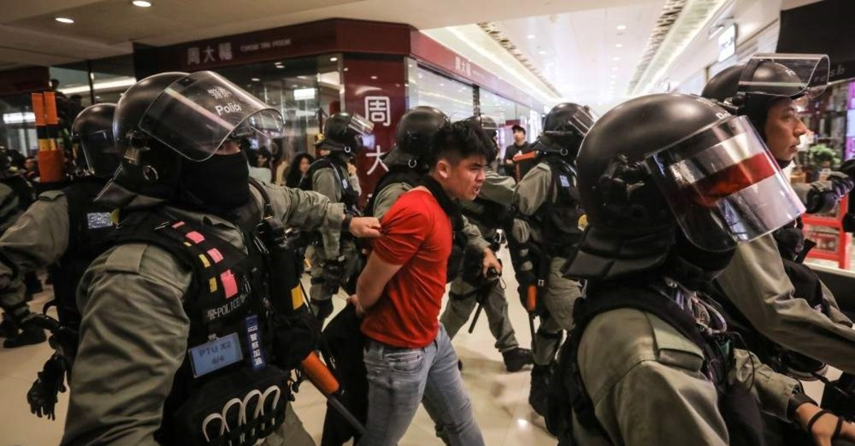 A riot police officer detains a protester after using pepper spray on him during a protest in Sheung Shui in Hong Kong, China, Dec. 28, 2019 (EPA Photo)