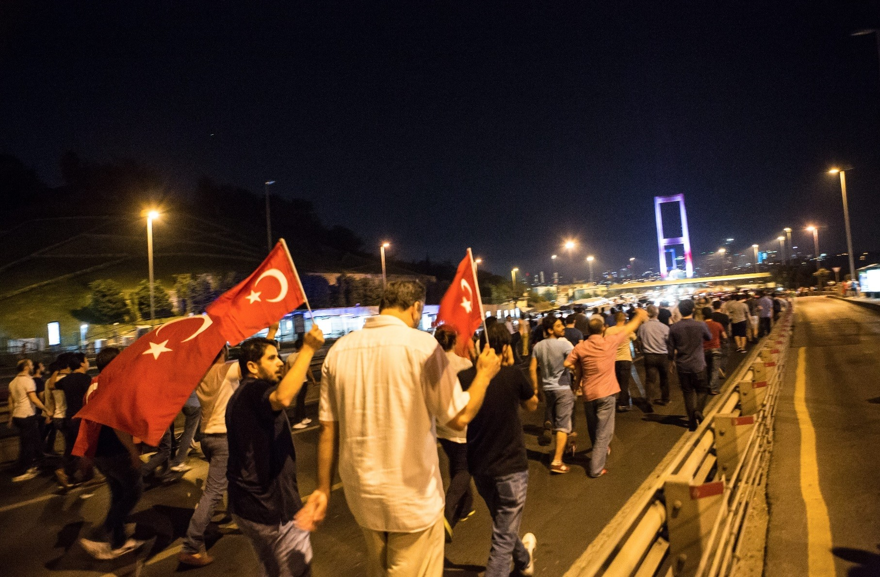 People holding Turkish flags march to the Bosporus Bridge in Istanbul on July 15, 2016.
