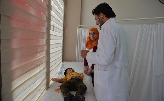 A Syrian doctor at Artuklu health center for Syrians attends to a patient.