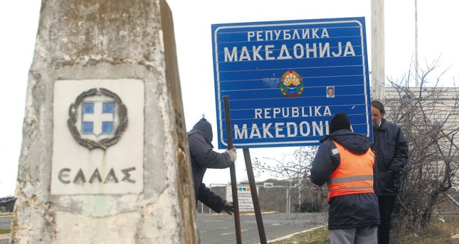 Workers remove a road sign that reads ''Republic of Macedonia'' – the other sign reads Hellas-Greece in Greek – on the southern border with Greece, near Gevgelija, Feb. 13, 2019.
