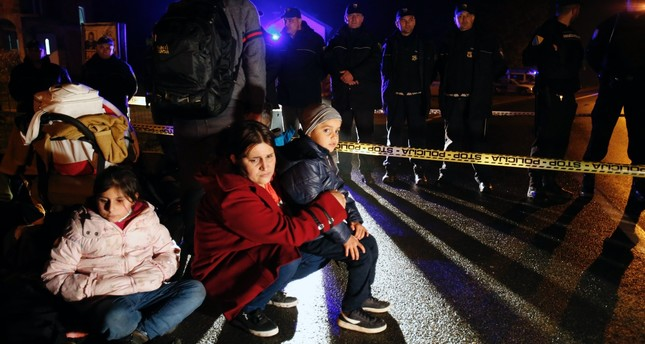 A migrant woman holds her child near a police barricade at the border crossing of Izacici, Bosnia, Oct. 22.