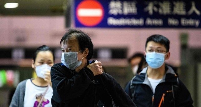 Passengers wear protective face masks  as they arrive from Shenzhen to Hong Kong at Lo Wu MTR station, hours before the closing of the Lo Wu border crossing in Hong Kong AFP Photo