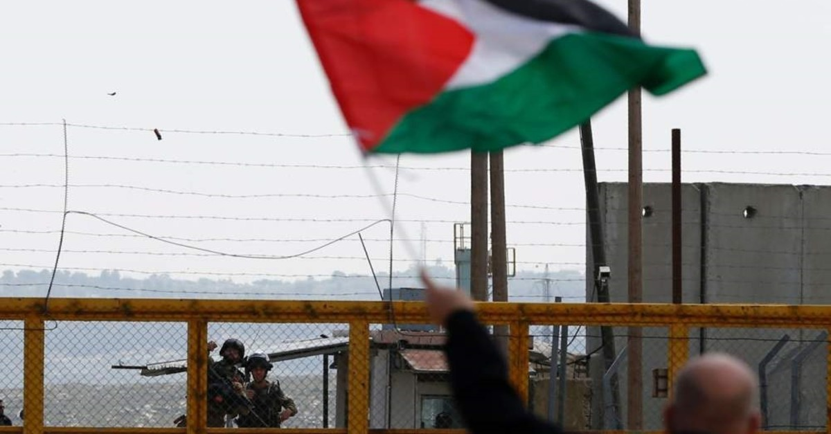 A Palestinian protester waves his national flag in front of Israeli security forces outside the compound of the Israeli-run Ofer prison in the Israeli occupied West Bank, March 30, 2016. (AFP Photo)