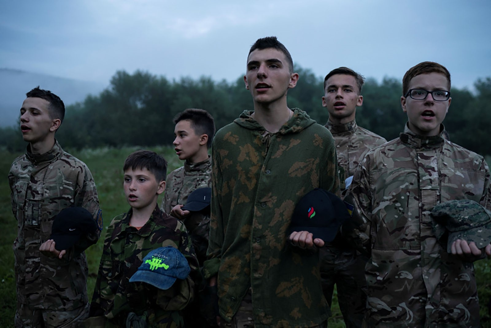 Mykhailo, 18, center, leads other young participants of the camp as they stand in formation singing nationalist songs.