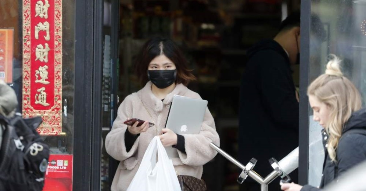 A woman wearing a face mask on her way out of a Chinese supermarket, Brighton, Feb. 11, 2020. (AP Photo)