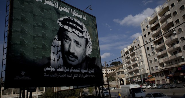 A youth plays soccer by a big poster of late Palestinian leader Yasser Arafat in the West Bank city of Ramallah, Friday, Nov. 8, 2013. (AP Photo)