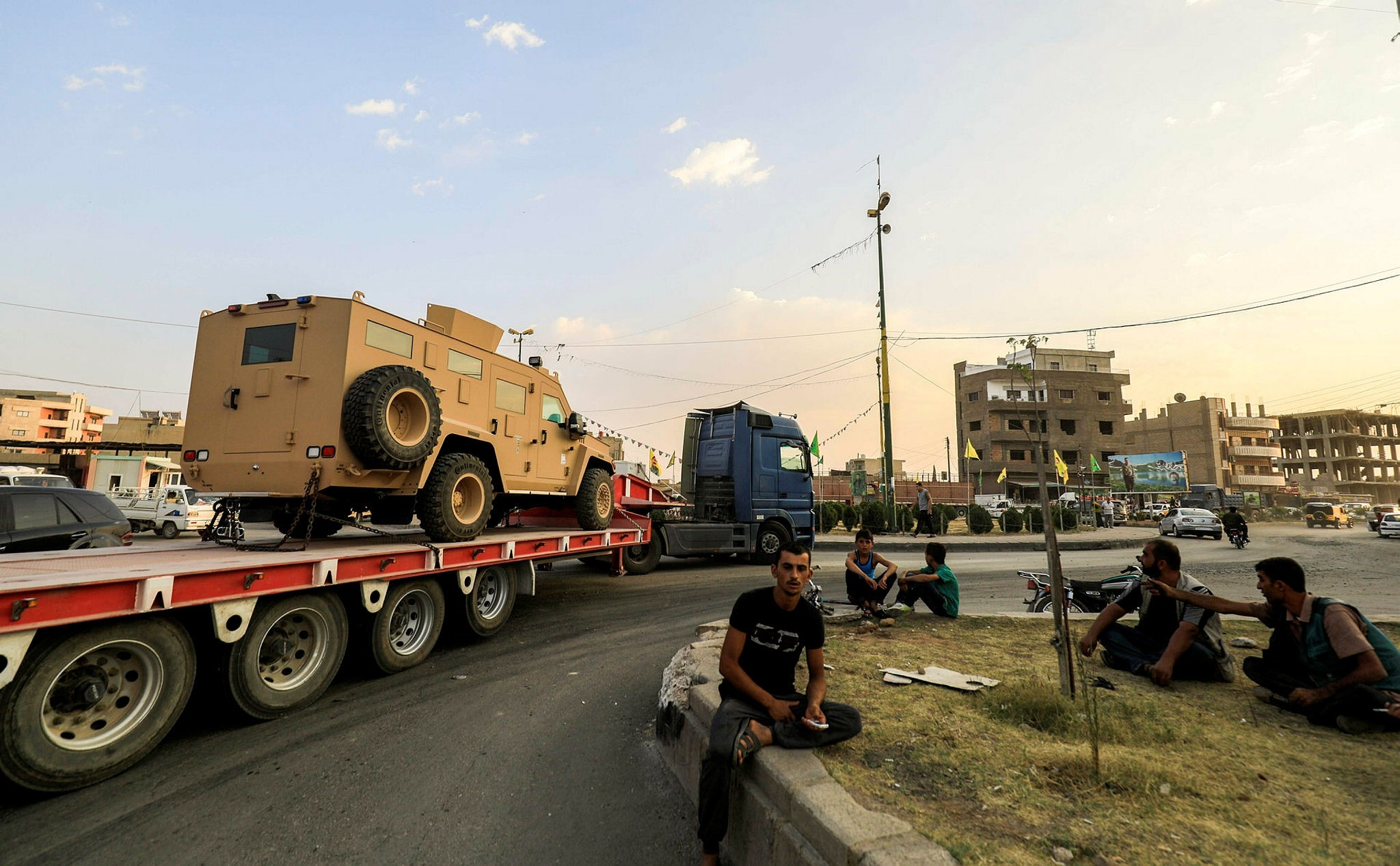 Men watch as a military convoy carrying US-made armored vehicles, bulldozers, and arms headed for YPG terrorists in Raqqa, passes through the northeastern Syrian city of Qamishli on September 19, 2017. (AFP file photo)