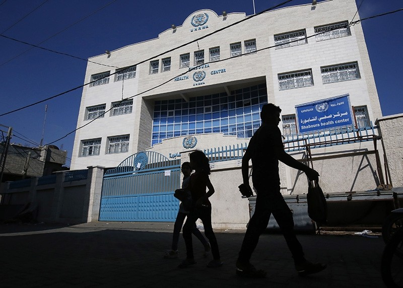 Palestinians walk past the closed offices of United Nations Relief and Works Agency (UNRWA) during a strike of all UNRWA institutions in Rafah in the southern Gaza Strip on Sept. 24, 2018. (AFP Photo)