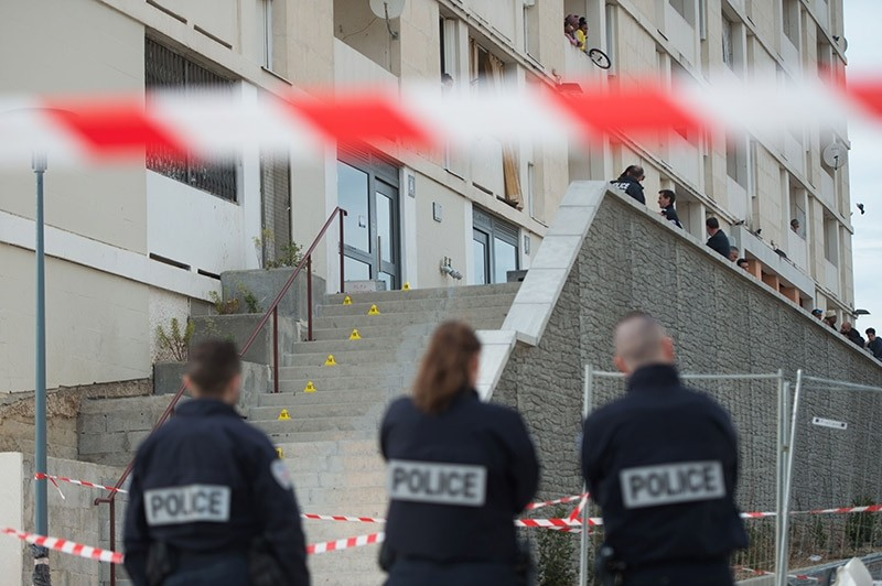Police officers stand guard at the entrance of an apartment block of the Cite des Lauriers in the northern 13th district of Marseille on March 18, 2017 (AFP Photo)
