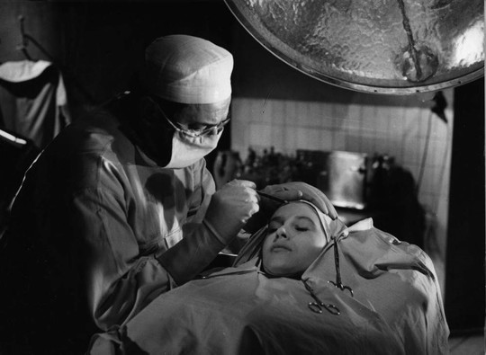 """Plastic surgeon Dr. Genessier operates on his daughter's face in the film ʺLes Yeux Sans Visage"""" (""""Eyes Without a Face"""")."""