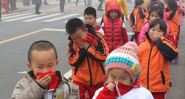 This photo taken Dec. 23, 2015, shows elementary school students covering their mouths and noses after the classes were suspended because of red alert for heavy smog in Binzhou, east China's Shandong province. (AFP Photo)