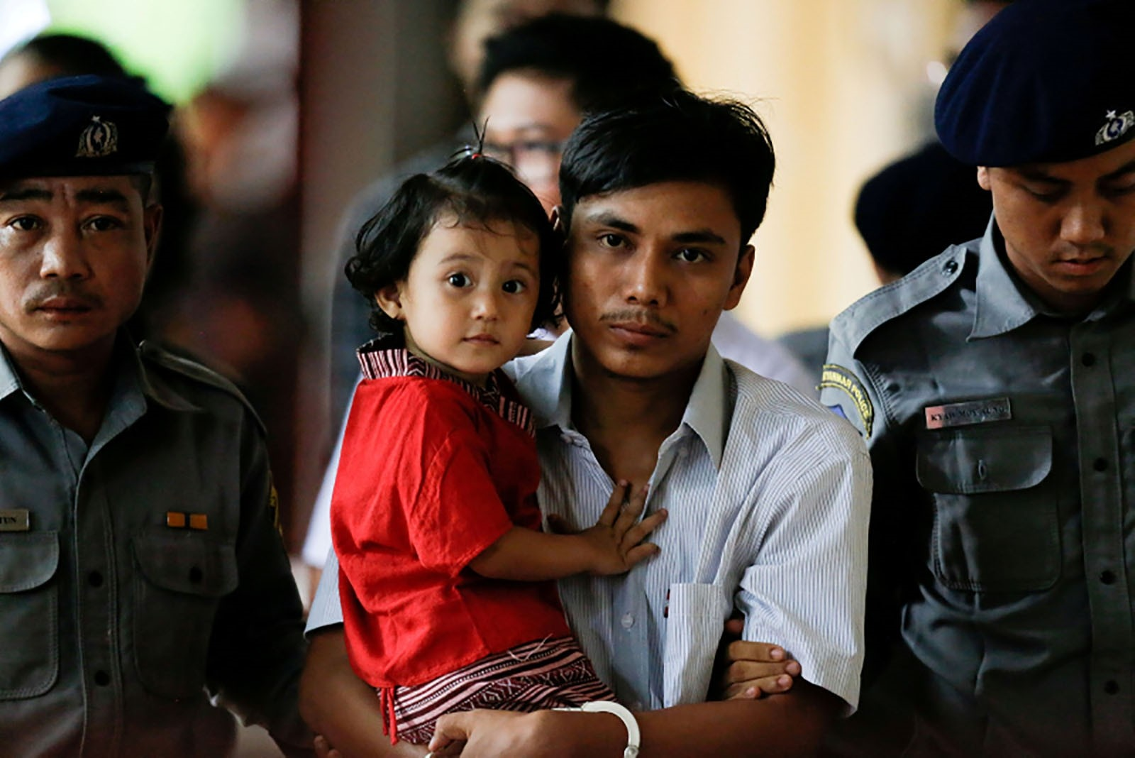 Detained Reuters journalist Kyaw Soe Oo carries his daughter Moe Thin Wai Zin while escorted by police during a court hearing in Yangon, Myanmar, June 5, 2018.