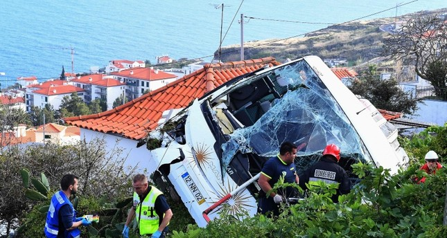 Firemen stand next to the wreckage of a tourist bus that crashed on April 17, 2019 in Caniço, on the Portuguese island of Madeira. (AFP Photo)