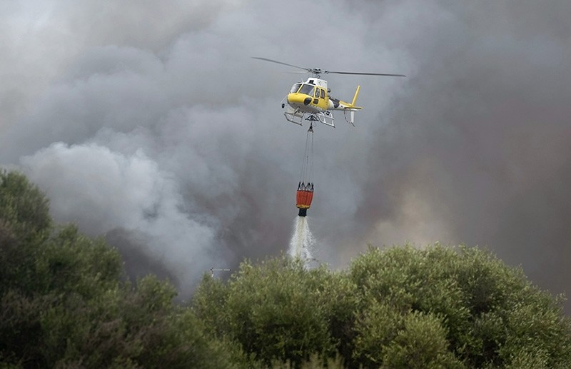 A helicopter dumps a load of water to extinguish a fire in Mahon, Menorca, Balearic Islands, Spain, 31 August 2017 (EPA Photo)