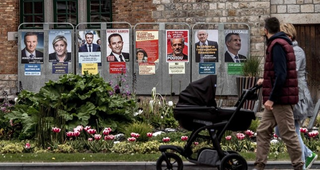People walking past campaign posters of French presidential election candidates in Bailleul, northern France, two days before the first round of the election.