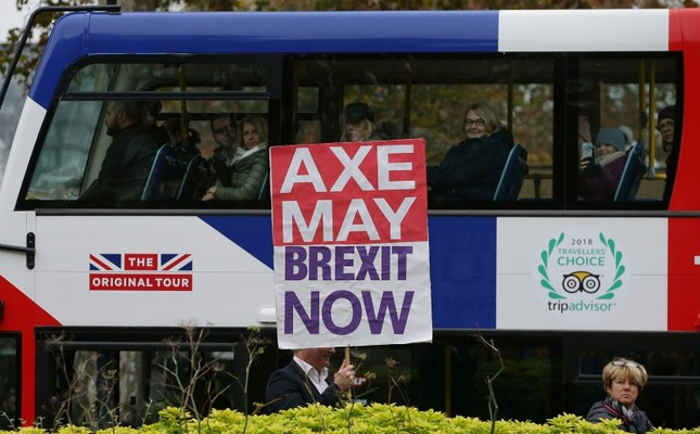 A pro-Brexit supporter stands with a placard demanding that Britain's Prime Minister Theresa May be sacked and to leave the European Union immediately near the Houses of Parliament in London on November 16, 2018. (AFP Photo)
