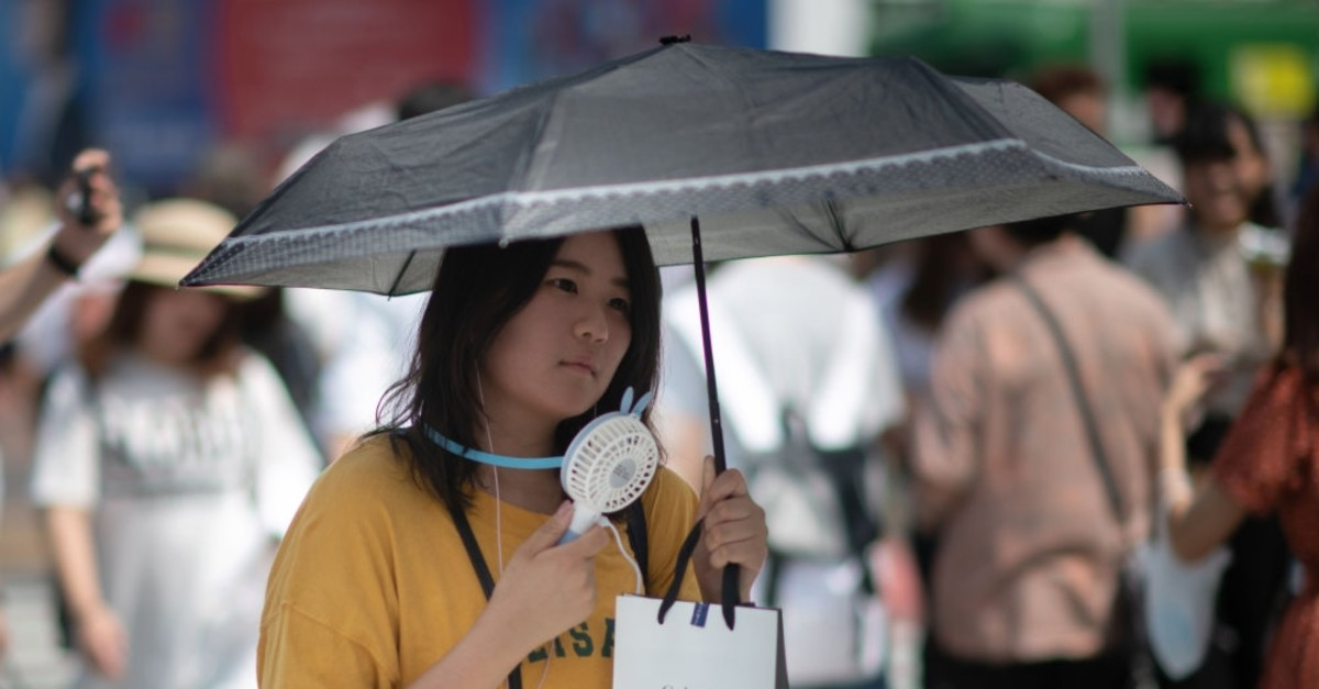 A woman uses a portable fan to cool herself in Tokyo during a heat wave in Japan.