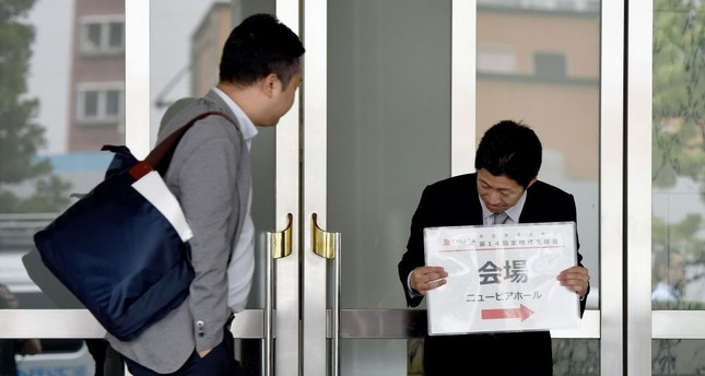 A staff member (R) holds a placard guiding shareholders to the venue of the annual shareholders' meeting of Japan's crisis-hit car parts maker Takata in Tokyo.