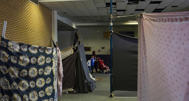 Migrants walk inside the disused Hellenikon airport, where refugees and migrants are temporarily housed, in Athens on May 22, 2017. (AFP Photo)