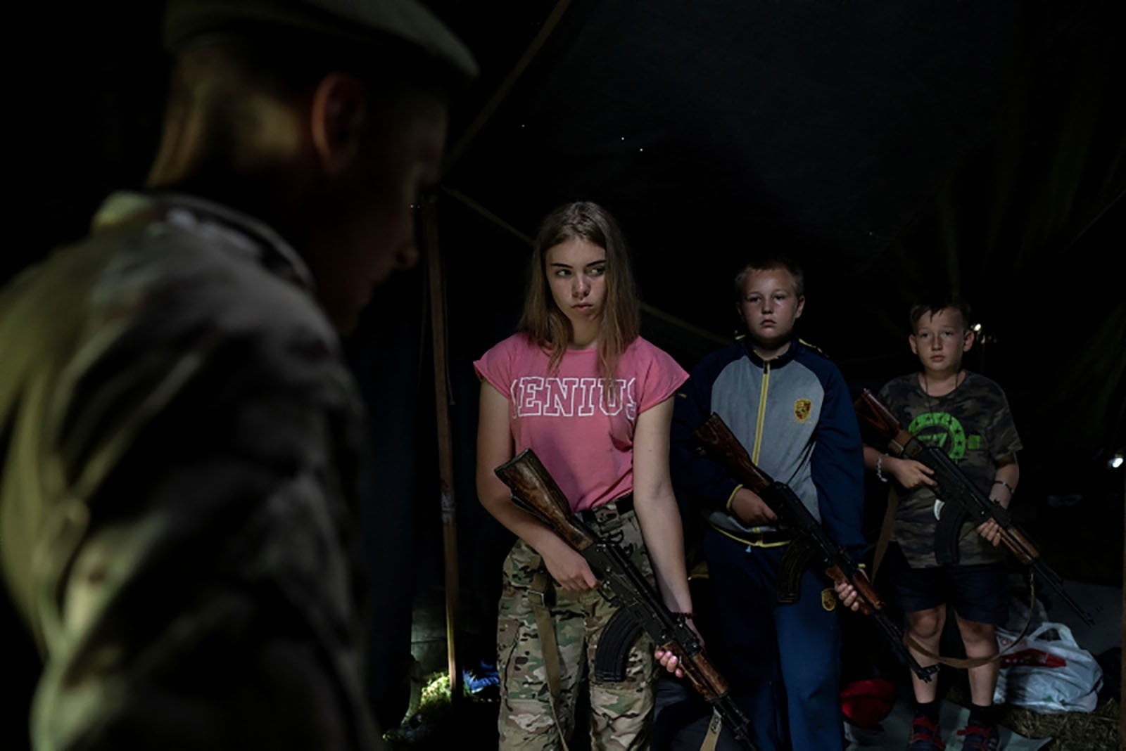 Participants of the camp hold their AK-47 rifles as they receive instructions during a tactical exercise.