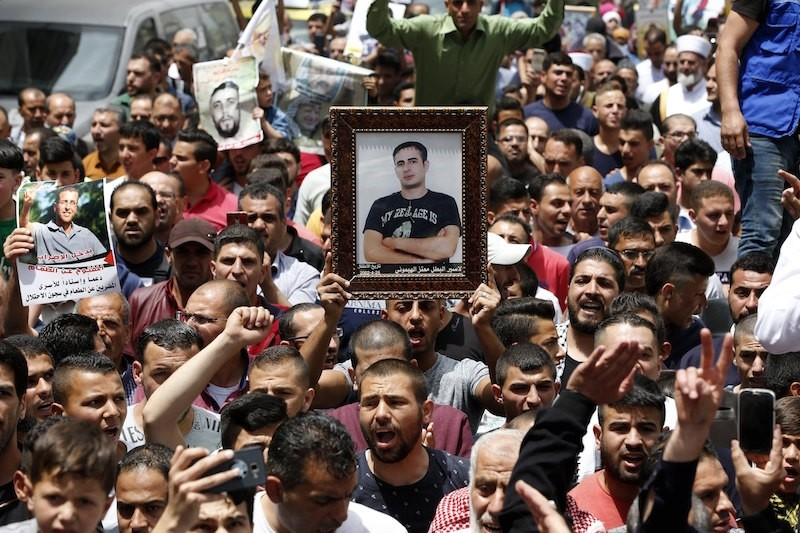 Palestinian hold pictures of their relatives who are prisoners in Israeli jails during a rally in support of prisoners in the West Bank city of Hebron. EPA Photo