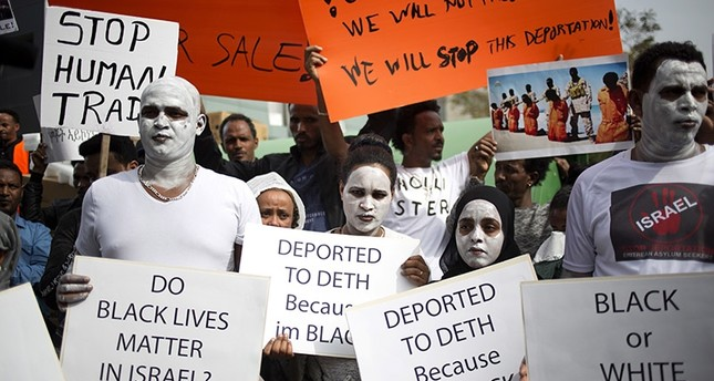 African migrants hold signs during a protest in front of Rwanda embassy in Herzeliya, Wednesday, Feb. 7, 2018. (AP Photo)
