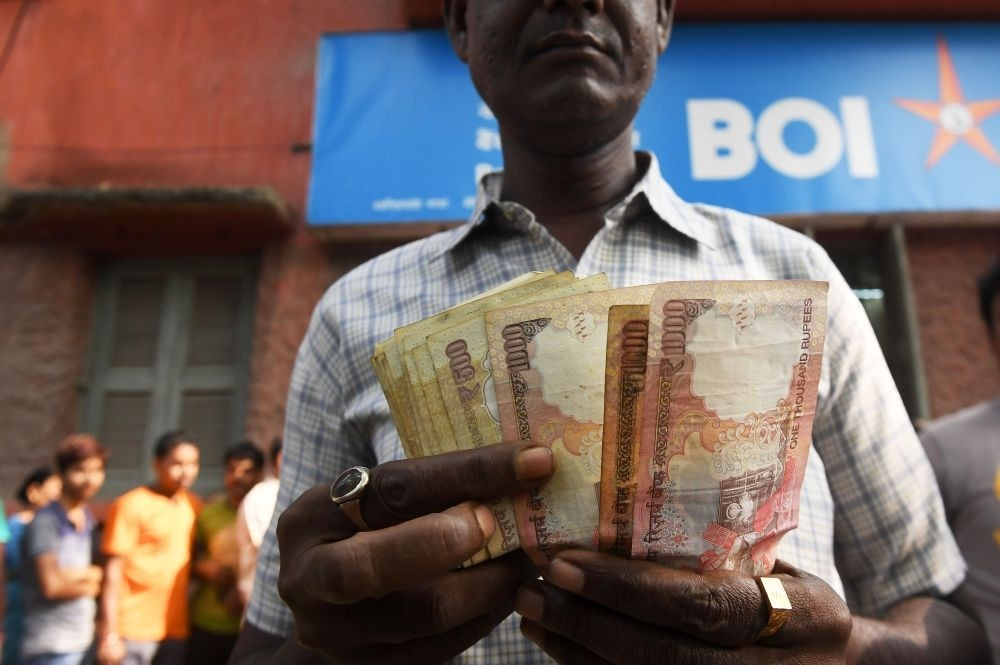 An Indian bank customer counts old rupee notes as he waits outside a bank to deposit and exchange them in Kolkata, last year.