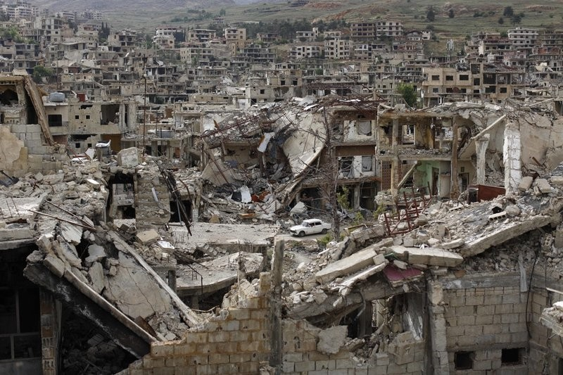 In this May 18, 2017 photo, a car passes by damaged streets at the mountain resort town of Zabadani in the Damascus countryside, Syria. (AP Photo)