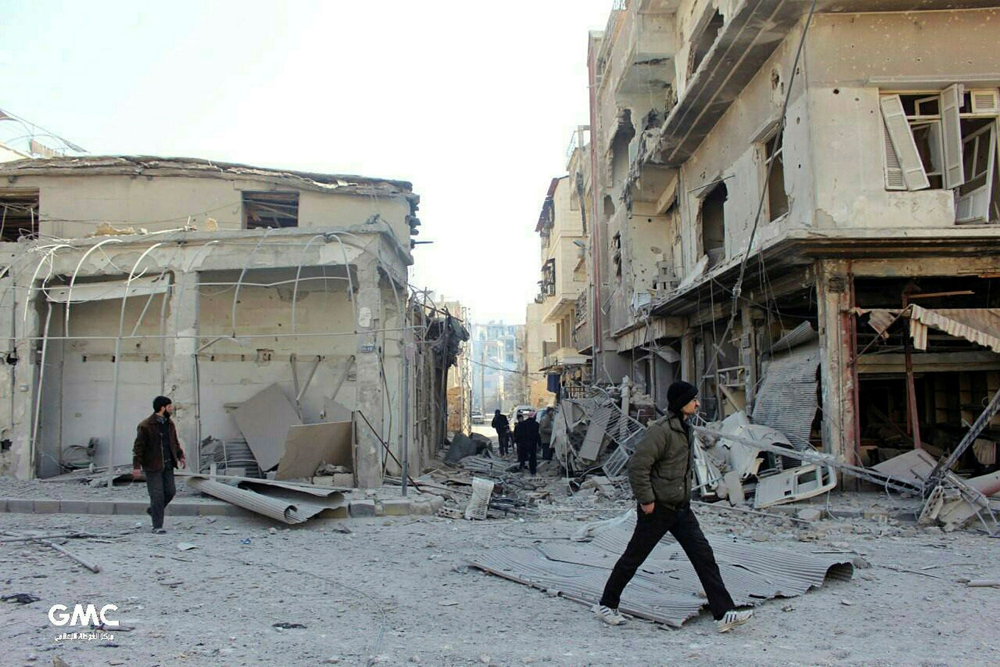 Syrians walking between destroyed buildings in Douma, after airstrikes and shelling by Syrian regime forces hit in the Eastern Ghouta region near Damascus, March. 1.