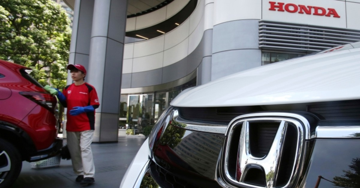 In this July 31, 2018 file photo, an employee of Honda Motor Co. cleans a Honda car displayed at its headquarters in Tokyo. (AP Photo)