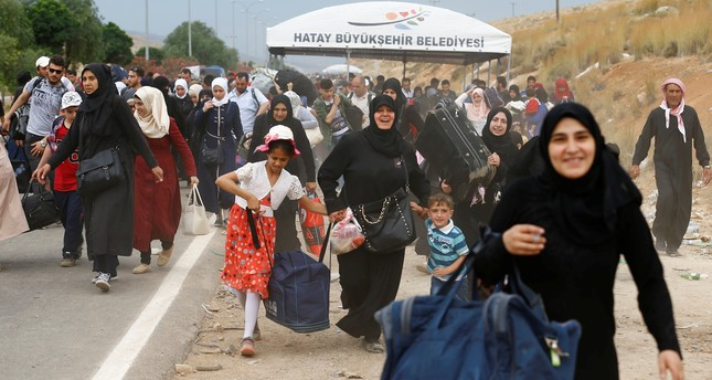 Syrians, who are returning to Syria ahead of Eid al-Fitr, carry their belongings as they walk to the Turkish Cilvegozu border gate in the southern Hatay province, Turkey June 14, 2017. (REUTERS Photo)