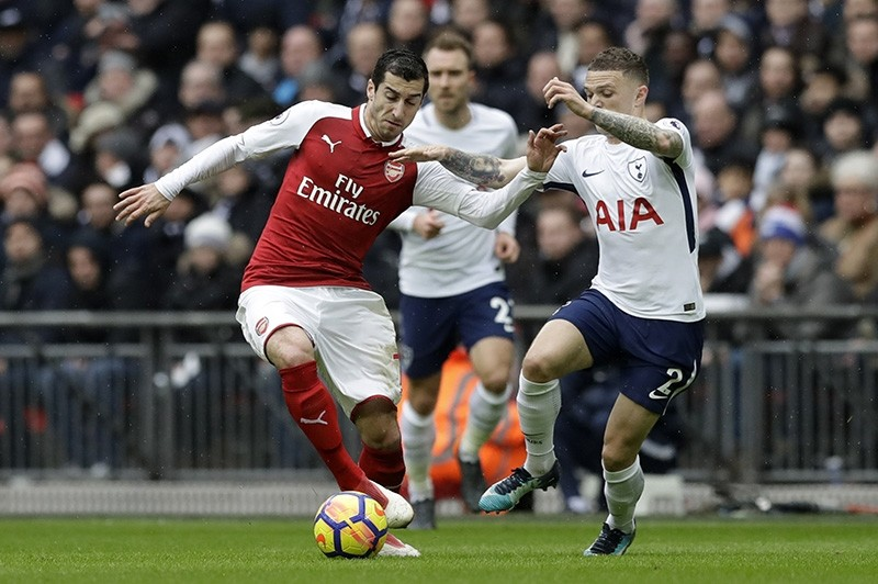 Arsenal's Henrikh Mkhitaryan, left is tackled by Tottenham Hotspur's Kieran Tripper during their English Premier League soccer match at Wembley stadium in London (AP File Photo)
