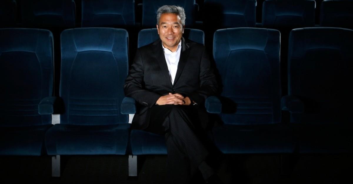 In this Feb. 6, 2013, file photo, Kevin Tsujihara, poses for photos in a screening room at the Warner Bros. Studios in Burbank, Calif. (AP Photo)